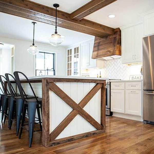 Urban farmhouse kitchen design with rustic beams, island, and metal stools. #hellolovelystudio #urbanfarmhouse #farmhousekitchen #modernfarmhousekitchen