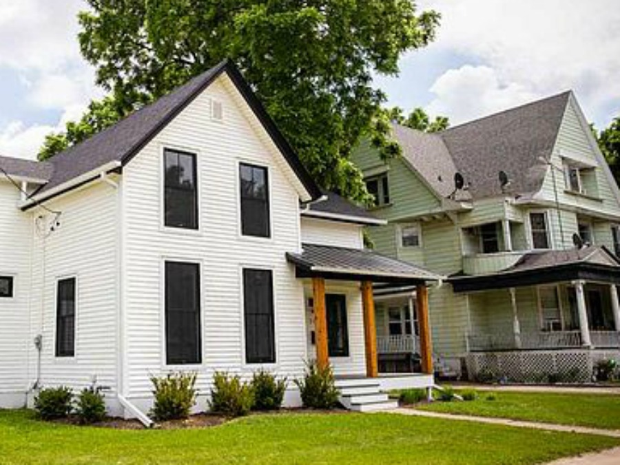 Charming 1900 renovated white urban farmhouse exterior in Beloit, WI with black windows, wood porch columns, and natural wood accents. #hellolovelystudio #urbanfarmhouse #houseexterior #modernfarmhouse #blackwindows