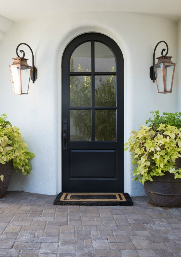 Black arched front door flanked by Old World  lanterns and white Stucco house exterior. Jaimee Rose Interiors.