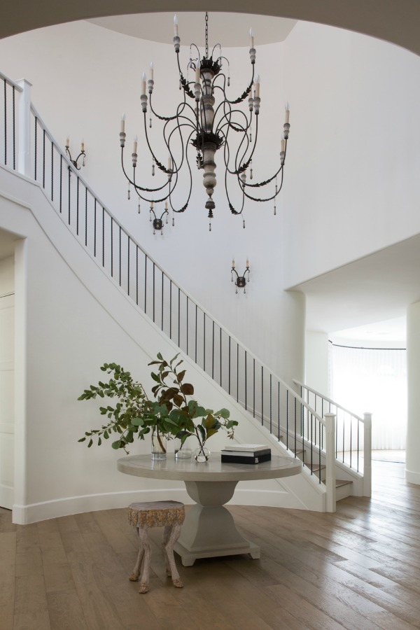Entry with snowy white walls, French country chandelier and wrought iron staircase - Jaimee Rose Interiors.