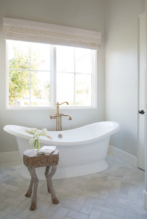 Beautiful white modern farmhouse bathroom with freestanding tub and herringbone tile floor - Jaimee Rose Interiors. #bathroomdesign #interiordesign
