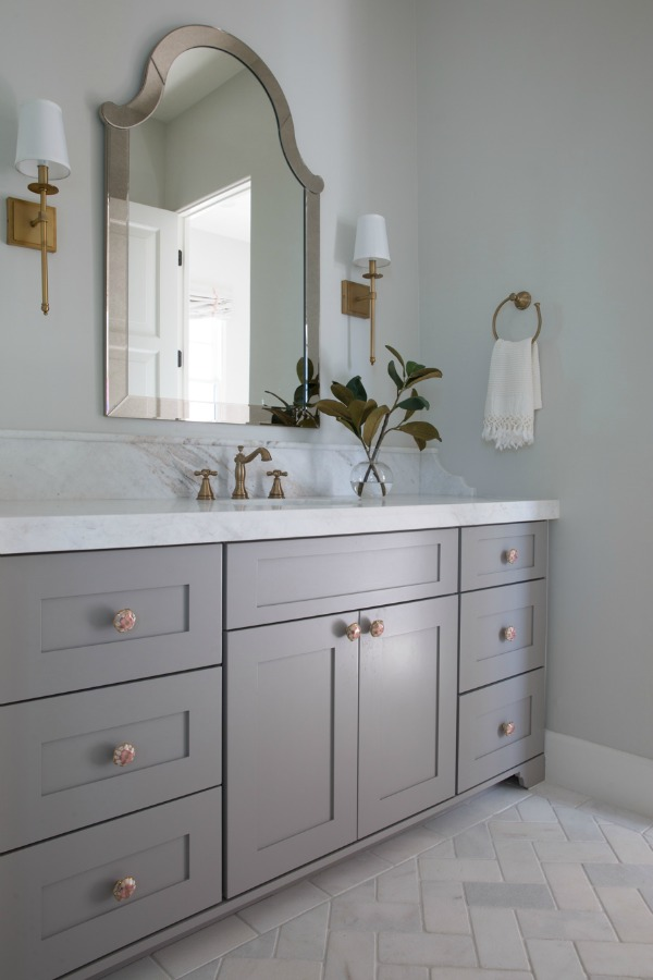 Beautiful modern farmhouse bathroom with grey vanity, brass fixtures and classic design by Jaimee Rose Interiors. #bathroomdesign #interiordesign
