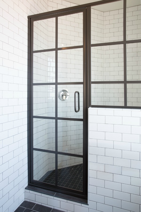 Black shower door and white subway tile in modern farmhouse style bathroom by Jaimee Rose Interiors.