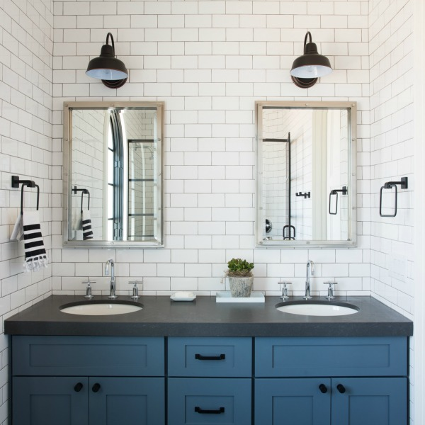 Modern farmhouse bathroom with blue double vanity, black counter, and white subway tile to celing on walls - Jaimee Rose Interiors.
