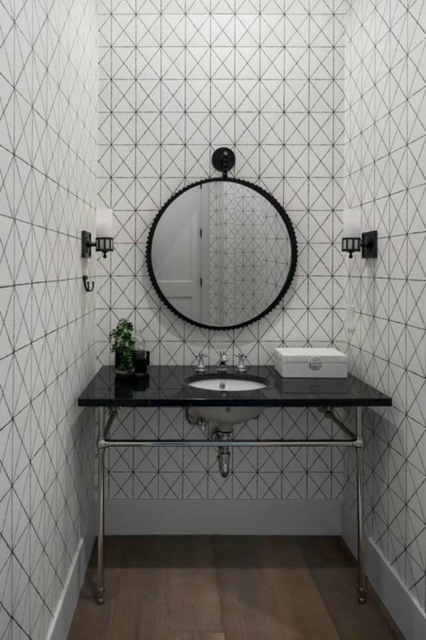 Modern bathroom design with black and white, console sink with black polished marble top, and round mirror.