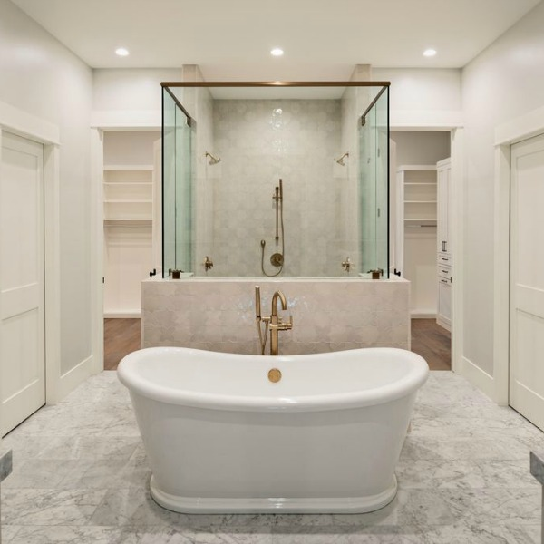 Luxurious white marble bathroom with glass enclosure for shower and soaking tub with brass fixtures - Jaimee Rose Interiors.