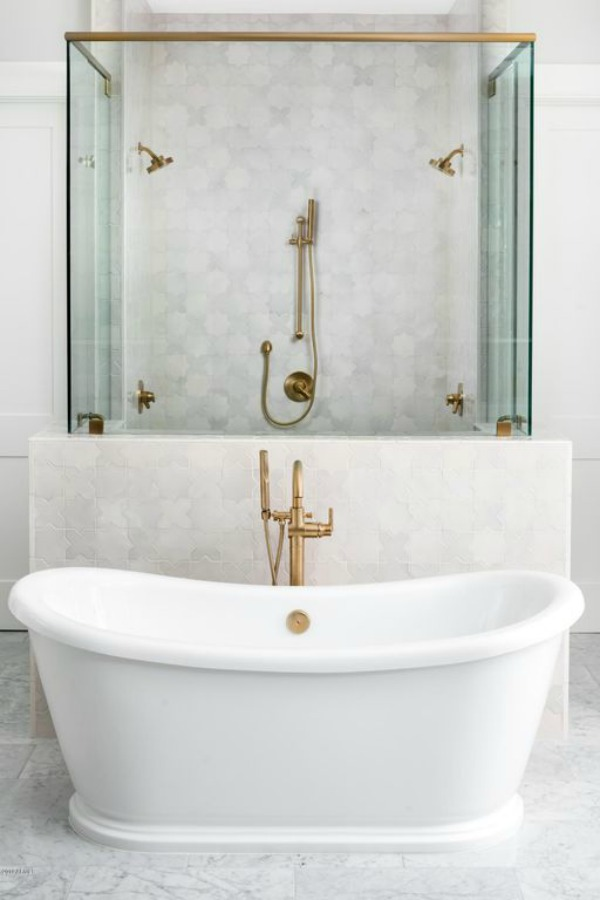 Beautiful white marble bathroom with soaker tub and brass fixtures - Jaimee Rose Interiors. #bathroomdesign #soakertub #brassfixtures