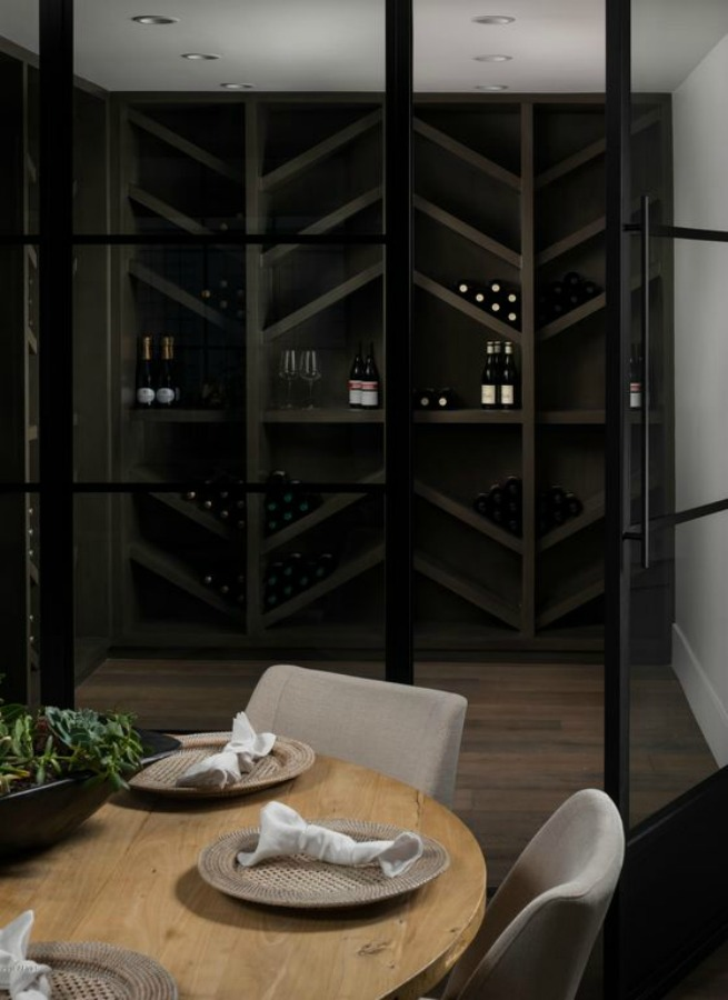 Wine cellar adjacent to a dining area with round table- interior design by Jaimee Rose Interiors.