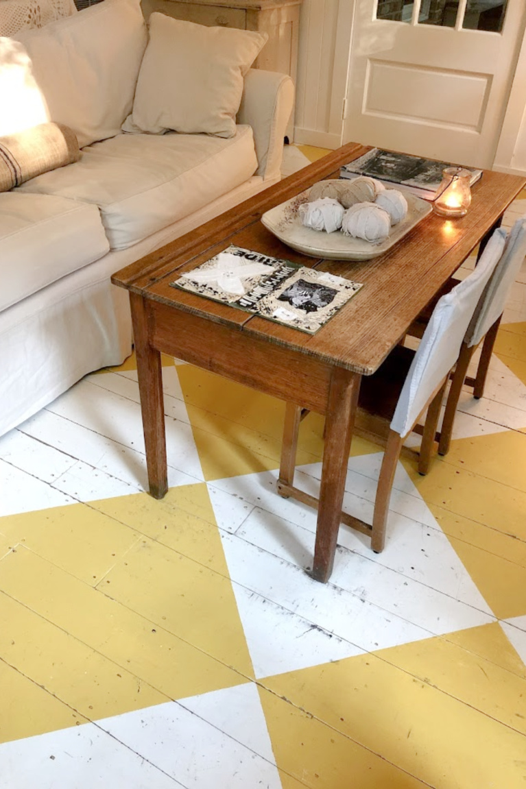 Lovely American country cottage living room in Leiper's Fork, TN, with yellow check wood floor, white decor and vintage, and art by Michele of Hello Lovely Studio.