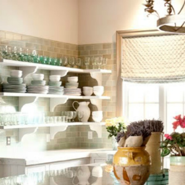 Open white kitchen shelves and green subway tiles in white French kitchen (Decor de Provence). Come tour French Fantasy House Build: A Timeless Tranquil Home Favorite!