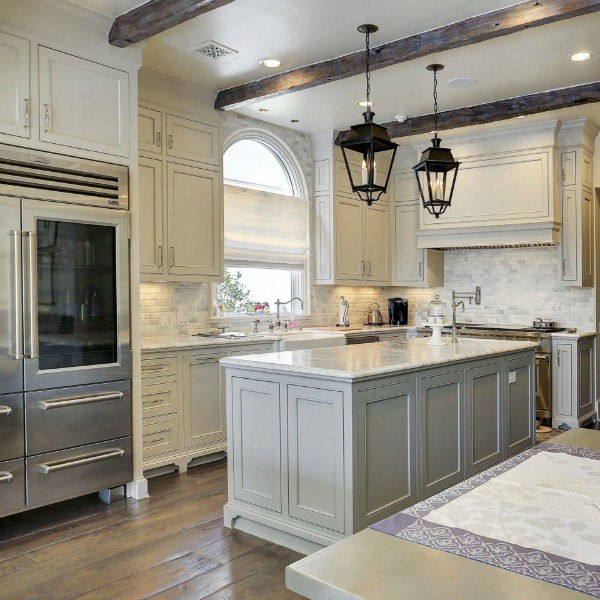 Sophisticated white and light grey French country kitchen with lantern pendants over island in a Houston home by Thomas O'Neill. #frenchcountry #kitchendesign #whitekitchen #traditionalkitchen
