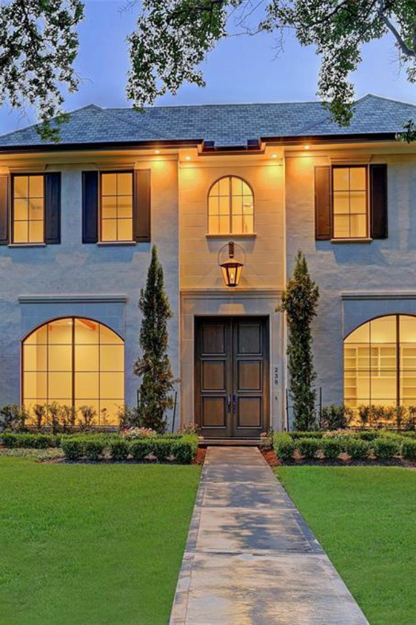 Exterior of a beautiful traditional Houston home with arched steel windows and lovely shutters.