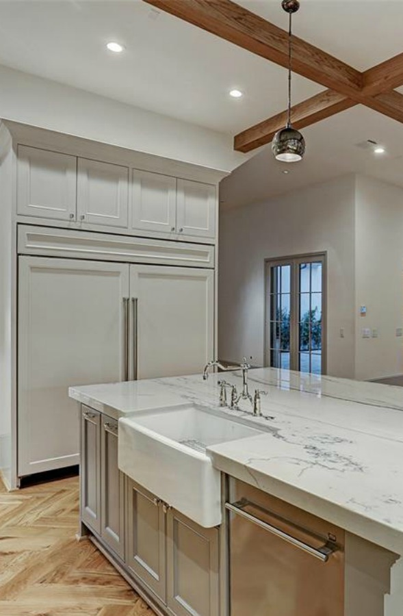Elegant and sophisticated light grey and white kitchen with ceiling beams and herringbone wood floor. #kitchendesign #frenchcountry #customhomedesign #greycabinets