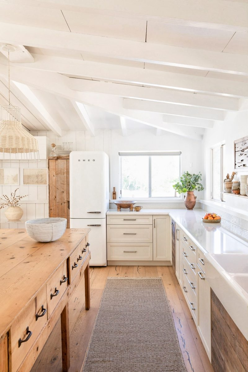 White kitchen with natural wood design elements for a cozy neutral mood - Lulu & Georgia. Come find 7 Simple Ideas to Add Smiles to White Rooms + Funny Quotes! #whitekitchen #modernfarmhouse #kitchendesign