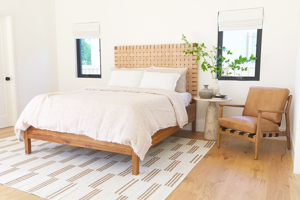 Serene white bedroom with neutrals, rustic accents, and woodsy warmth - Lulu and Georgia. #bedroomdesign #modernrustic #californiafarmhouse