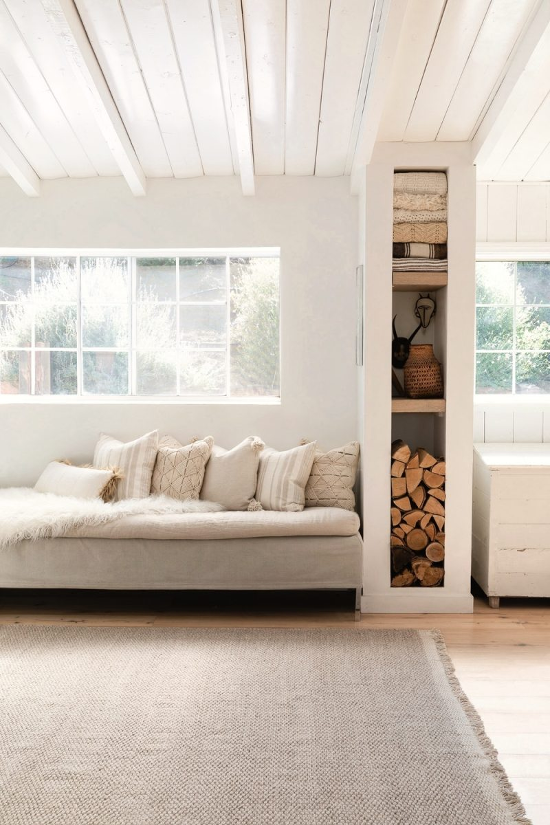 Linen daybed under sunny window and tower of shelves in a rustic zen modern farmhouse kitchen with white rafters and wood floors - Lulu & Georgia. #kitchendesign #rusticzen #modernfarmhouse #windowseat