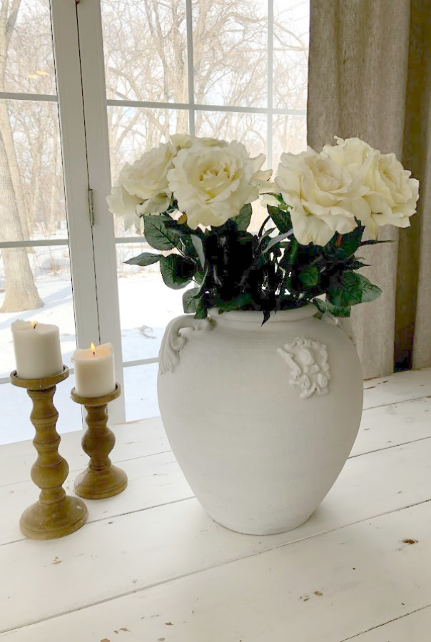 White roses in white terracotta urn on my white painted farm table in the kitchen - Hello Lovely Studio.