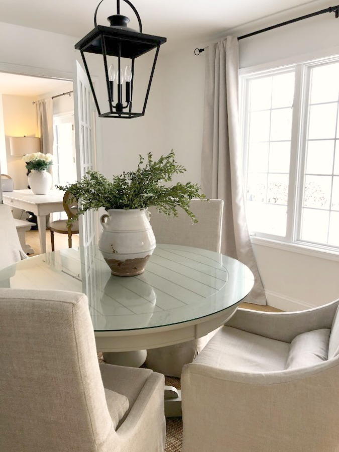 Belgian linen slope arm chairs around round dining table in our home - Hello Lovely Studio. #diningroom #modernfarmhouse #belgianlinen #interiordesign