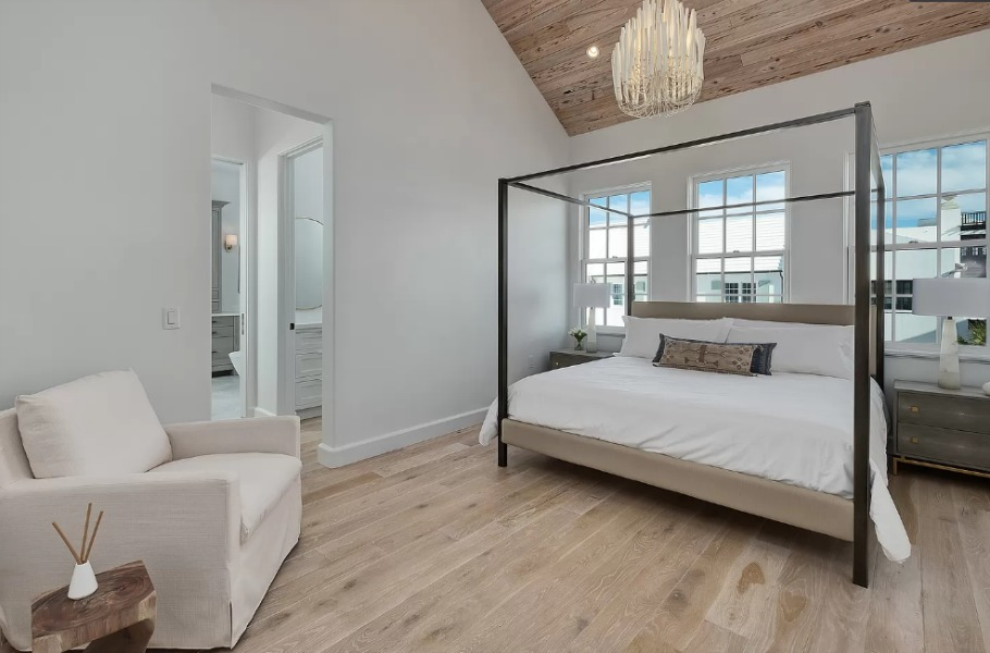 Warm minimal modern bedroom with vaulted ceiling clad in wood and light hardwood flooring - design by Domin Bock. #bedroomdecor #coastalbedroom #luxuriousbedroom #interiordesign #woodceiling