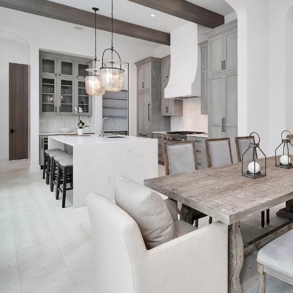 Understated, muted neutrals in a luxurious kitchen and breakfast room of a coastal home (Alys Beach) by Domin Bock. #kitchendesign #warmminimal #luxuriouskitchen #greycabinets #customkitchen