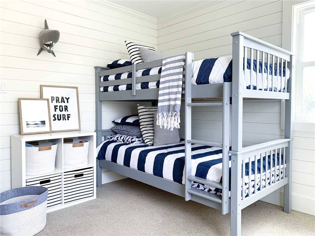 Charming blue and white classic coastal bedroom with shiplap - Summerfell Cottage in NC. #bunkroom #coastalstyle #shiplapwall #blueandwhite #interiordesign #bedroomdecor