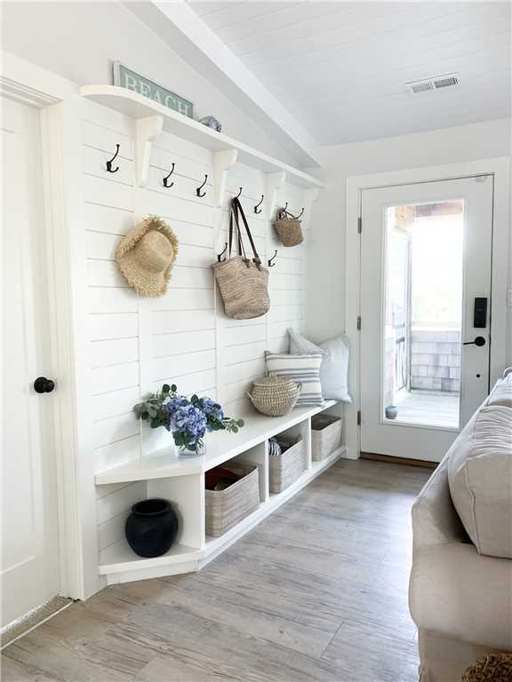 Charming entry with hooks and cubbies in a coastal cottage in NC called Summerfell. #coastalcottage #interiordesign #builtins #mudroom
