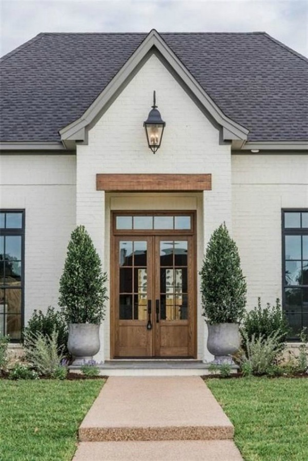 Beautiful white painted brick house exterior with natural wood double door entrance - AACMM. #housedesign #whitebrick #curbappeal