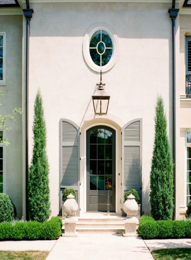 Luxurious and custom white stucco home with arched door and shutter entry - Daigh Rick Landscape Architects. #whitestucco #housedesign #curbappeal #shutters