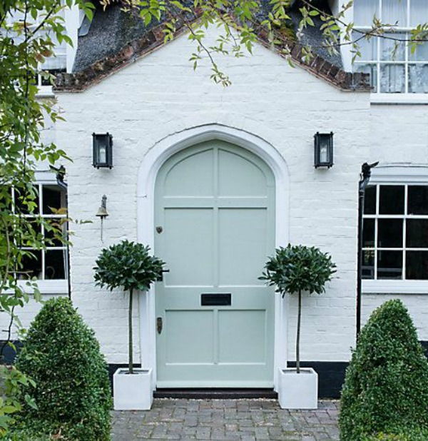 Magnificent white brick house exterior with soft minty green arched front door and pair of bay trees - John Lewis. #whitebrick #housedesign #curbappeal #houseexteriors
