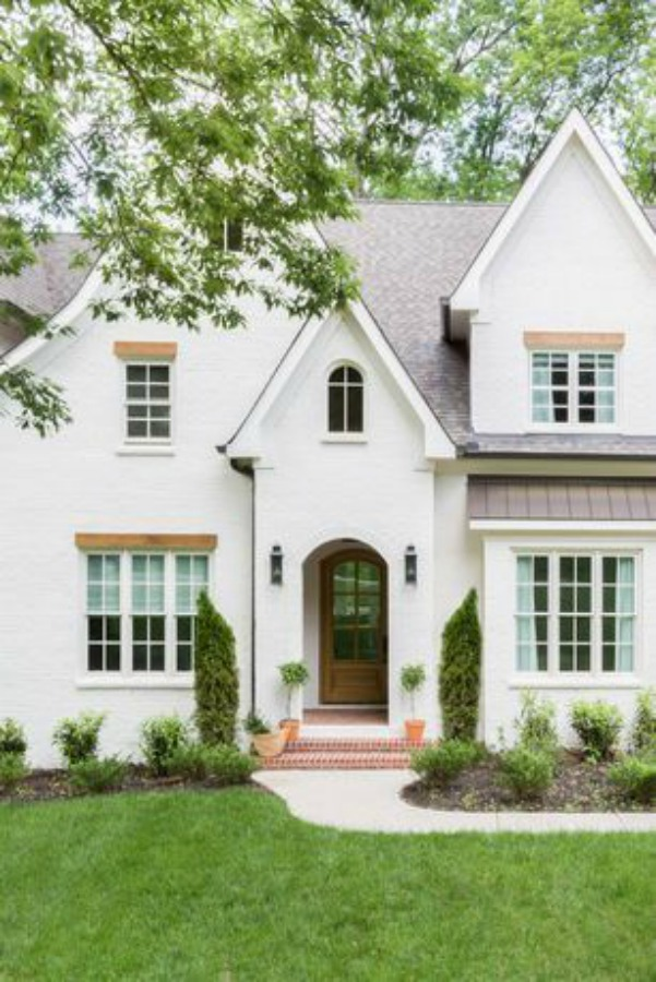 Magnificent white Tudor style home exterior with arched front doorway - Scout & Nimble. #whitehouseexterior #housedesign #tudorstyle