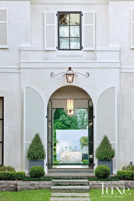 Magnificent white home exterior with arched shutters and magnificent lantern - Luxe Home. #houseexterior #housedesign #shutters
