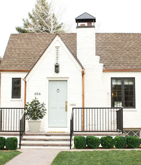 Beautiful white Tudor home exterior in Denver by Studio McGee with brick painted Benjamin Moore China White and front door Greyhound. #whitebrick #studiomcgee #bricktudor #houseexterior #benjaminmoorechinawhite #benjaminmooregreyhound #paintcolors
