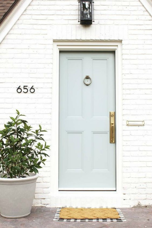 Beautiful white Tudor home exterior in Denver by Studio McGee - paint color on brick: Benjamin Moore China White and paint on door: Benjamin Moore Greyhound. #paintcolors #benjaminmooregreyhound #benjaminmoorechinawhite #houseexterior #whitebrickhouse #housedesign