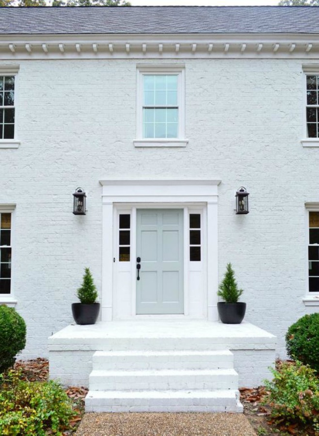 White brick house exterior with pastel front door - Young House Love. #whitebrick #houseexterior #paintedbrick #sherwinwilliamsmodernewhite #benjaminmooretranquility