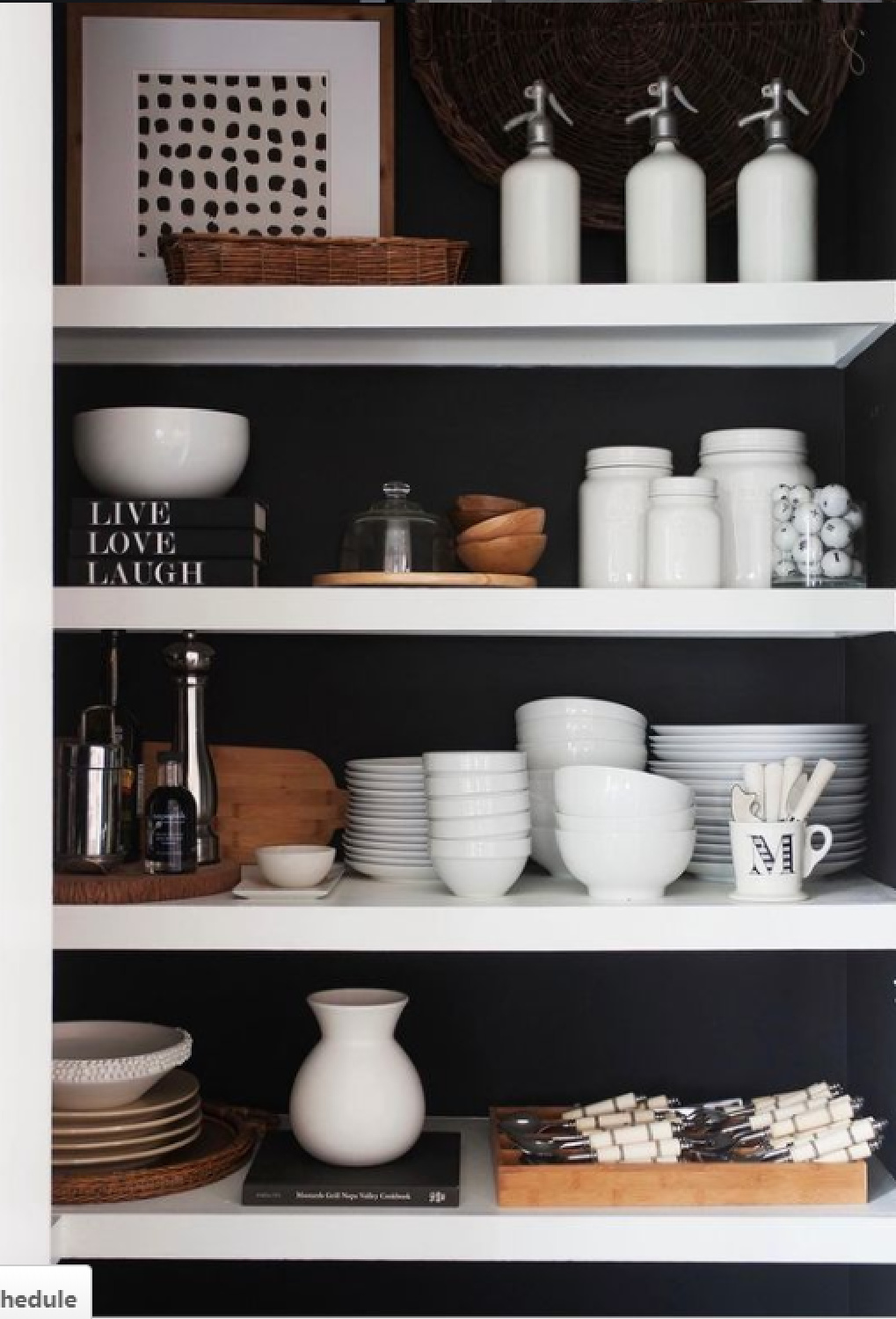 White pantry shelves contrast with black painted wall for a dramatic effect in a kitchen - design by Sherry Hart. #blackandwhite #pantry #blackwalls #interiordesign