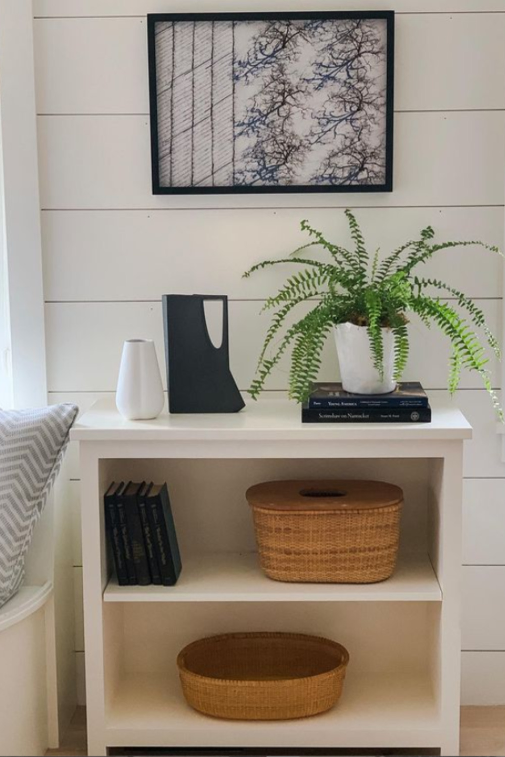 Black and white vignette with white shelves, shiplap, and black accents - design by Sherry Hart. #modernfarmhouse #interiordesign #blackandwhite