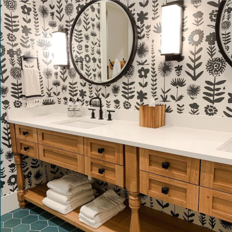 Traditional bathroom design with a fresh twist: black and white bold graphic Schumacher 1889 wallpaper, custom console table style double vanity, round mirrors, and green hex floor tiles. Design by Sherry Hart. #blackandwhite #bathroomdesign #classicstyle #traditionalstyle