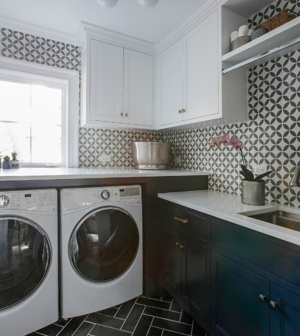 Laundry room with bold tiled walls and blue cabinets - Edward Deegan Architects. #laundryroom #blueandwhite #bluecabinets