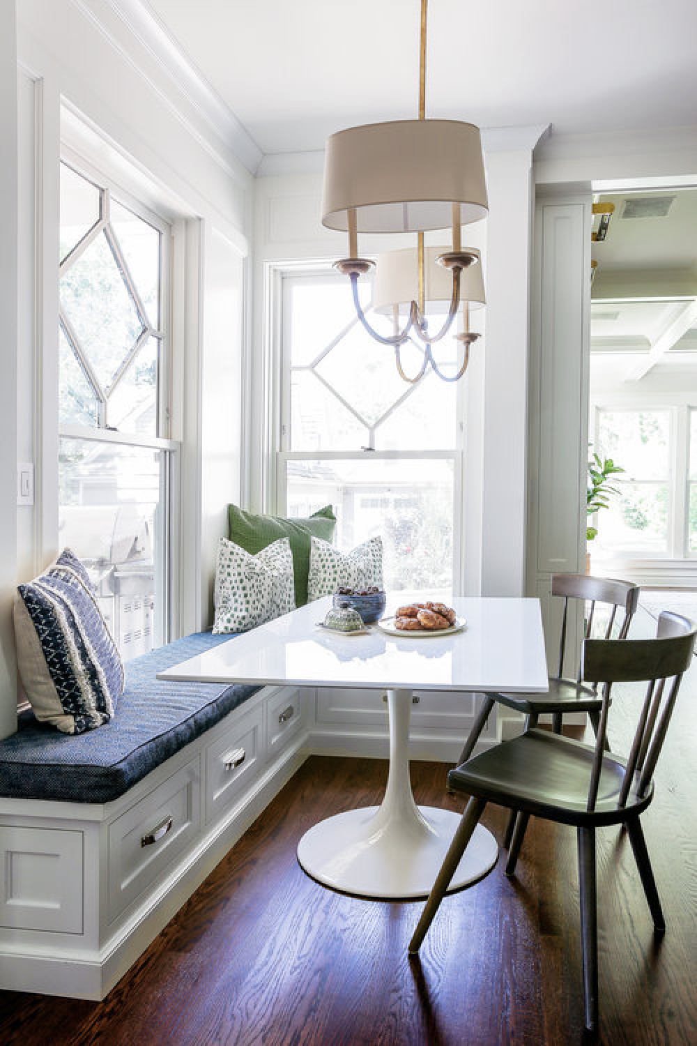 Classic style in a breakfast nook of a traditional white kitchen with blue accents, custom millwork, and built-in window seat - Edward Deegan Architects.