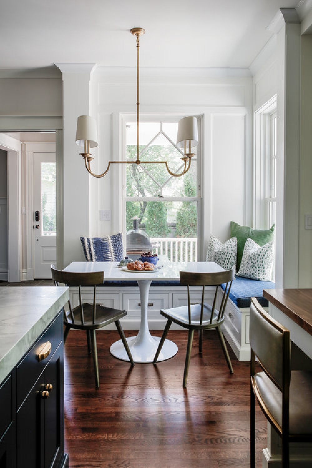 Lovely breakfast nook with built-in window seat and modern Saarinen style table in a blue kitchen by Edward Deegan Architects.
