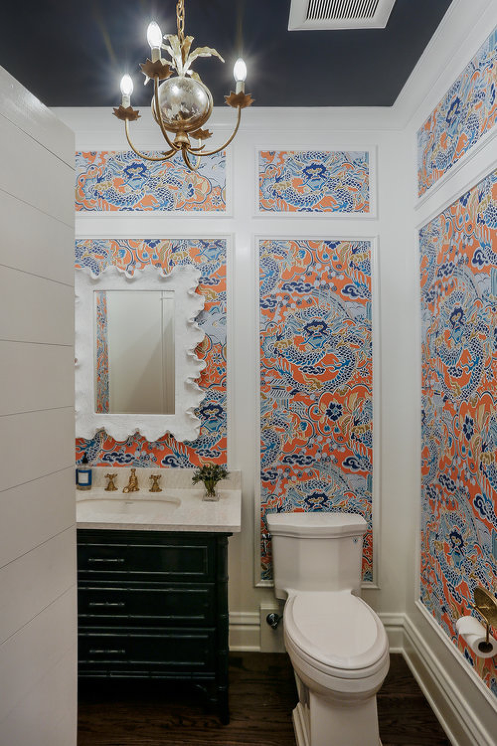Traditional style powder bathroom design with custom millwork, wallpaper with blue accents, and design by Edward Deegan Architects.