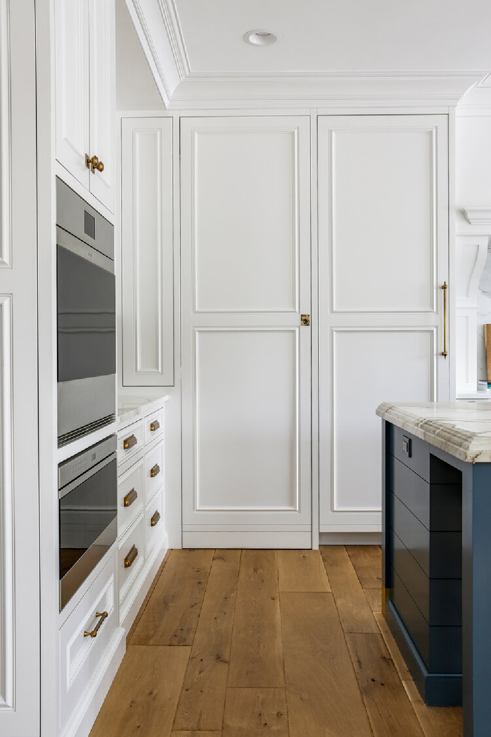 Classic white kitchen with custom cabinets, wall ovens, and blue accents - Edward Deegan Architects. Find more blue kitchen ideas in this story!