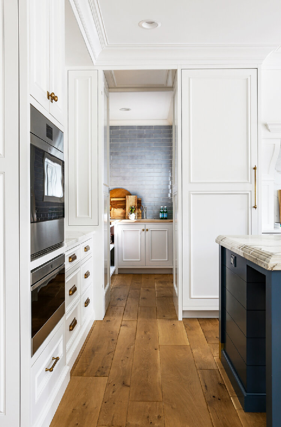 White Shaker cabinets in a classic kitchen by Edward Deegan Architects. Find more blue kitchen ideas in this story! #shakercabinets #classickitchen #wallovens