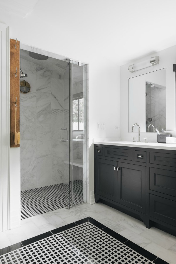 Timeless, traditional, and classic, this black and white modern farmhouse bath by Edward Deegan feels approachable yet luxurious. #modernfarmhouse #interiordesign #blackandwhite #bathroomdesign