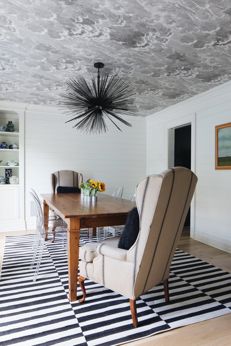 Wallpapered ceiling and black and white stripe rug anchor this eclectic dining room in a modern farmhouse by Edward Deegan Architects. #modernfarmhouse #interiordesign #blackandwhite #diningroom #striperug #wallpaperedceiling