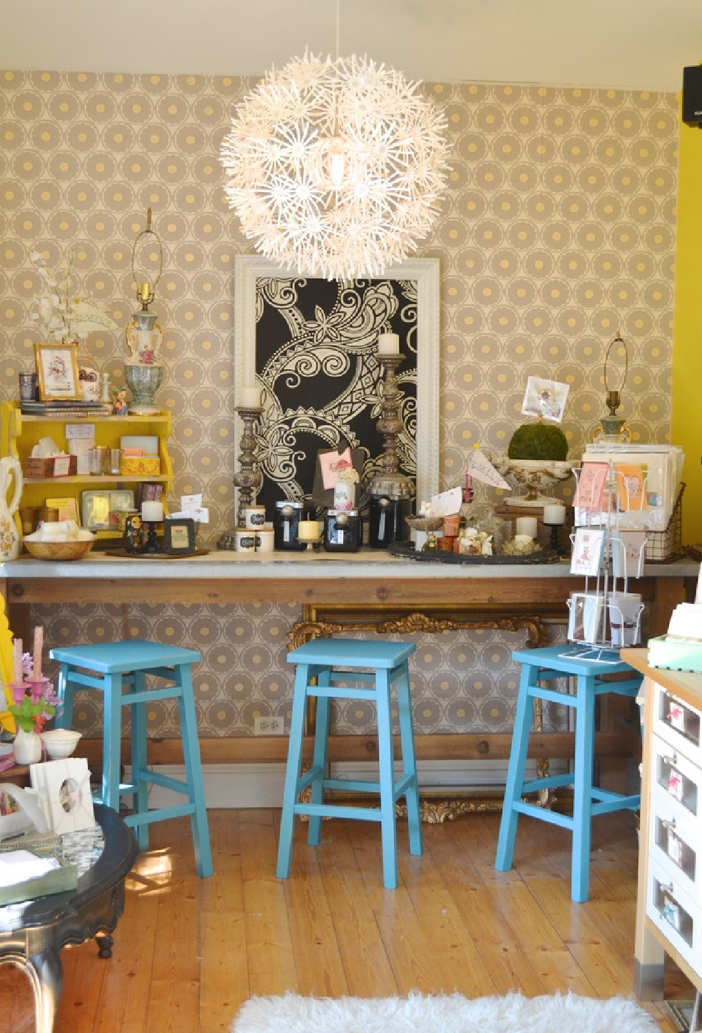 Whimsical bar with cheerful blue stools in a boho fun art studio with yellow accents - Jenny Sweeney.
