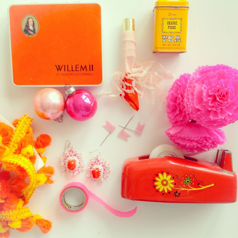 Cheerfully bold pink and orange vintage objects are gathered in a beachy 70's boho vignette by Jenny Sweeney.