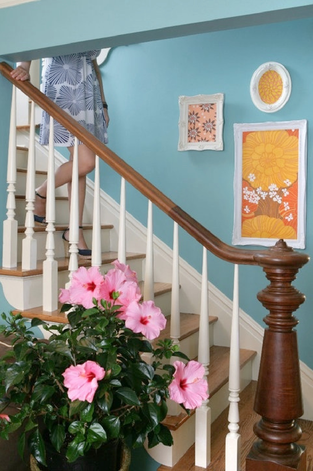 Turquoise beachy wall paired with traditional wood staircase in the beachy boho groovy living room of Jenny Sweeney.