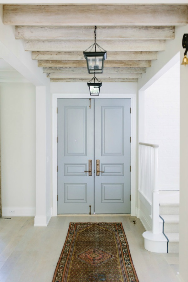 Serene entry with pale grey doors and wood rafters in a lovely home by Kate Marker in Barrington, IL. Come enjoy encouraging love quotes and timeless decor inspiration!#interiordesign #entry #greydoors #serenedecor