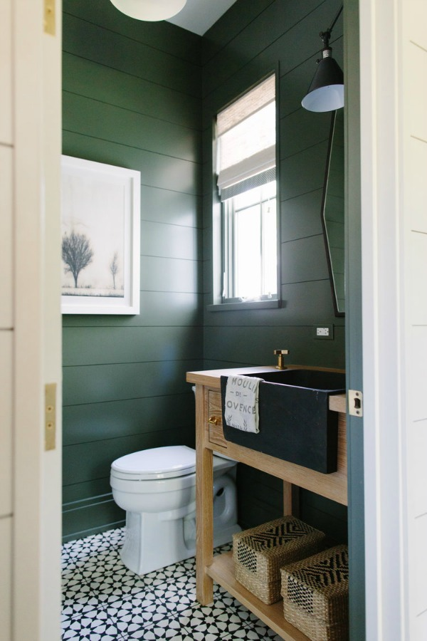 A moody deep dark green paint covers shiplap clad walls in a powder bath with farm sink by Kate Marker in Barrington, IL. Come enjoy encouraging love quotes and timeless decor inspiration! #interiordesign #bathroomdesign #shiplap #greenpaint #darkgreen